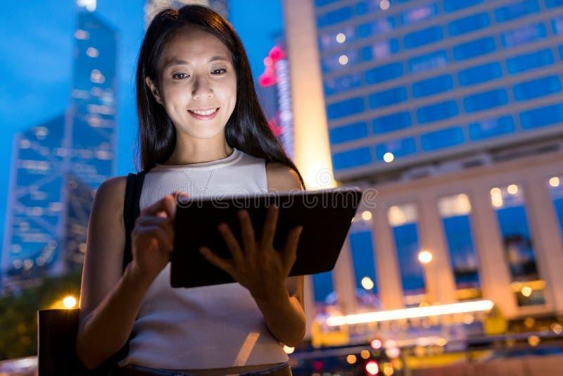 工作在数字式片剂的女商人在城市在晚上 库存照片