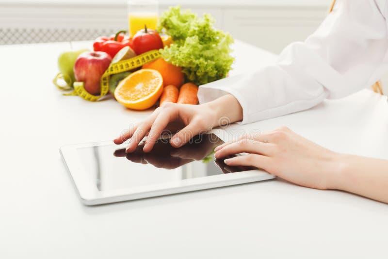 工作在数字式片剂的女性营养师 图库摄影
