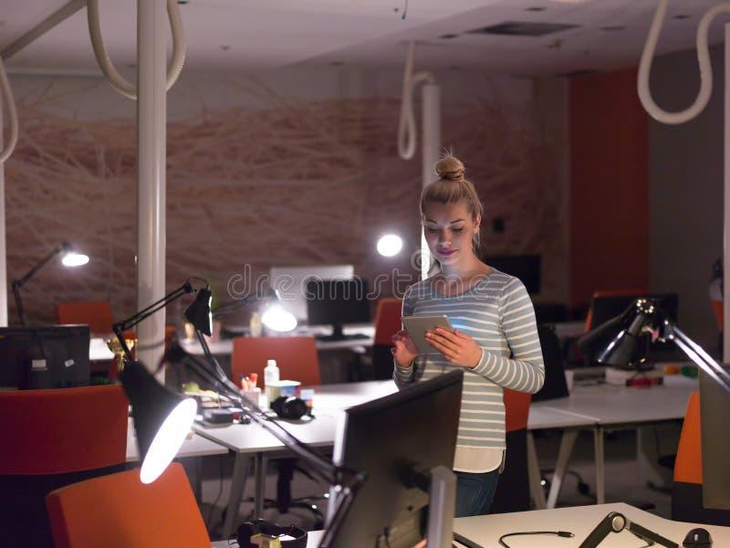 工作在数字式片剂的妇女在夜办公室 图库摄影