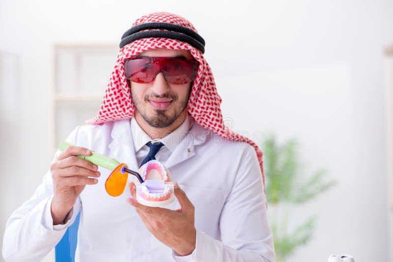 工作在新的牙植入管的阿拉伯牙医 库存照片