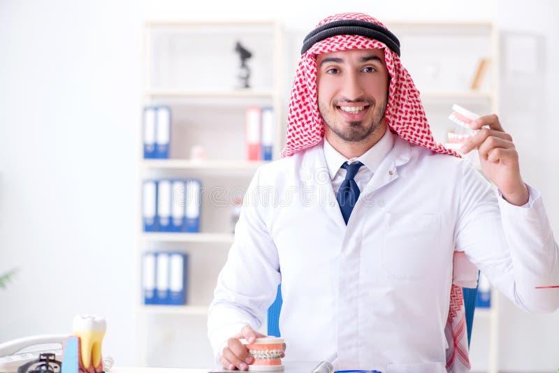 工作在新的牙植入管的阿拉伯牙医 免版税库存照片