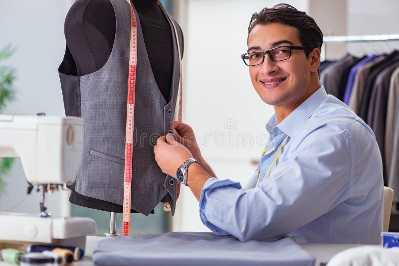 工作在新的衣物的年轻人裁缝 免版税库存图片