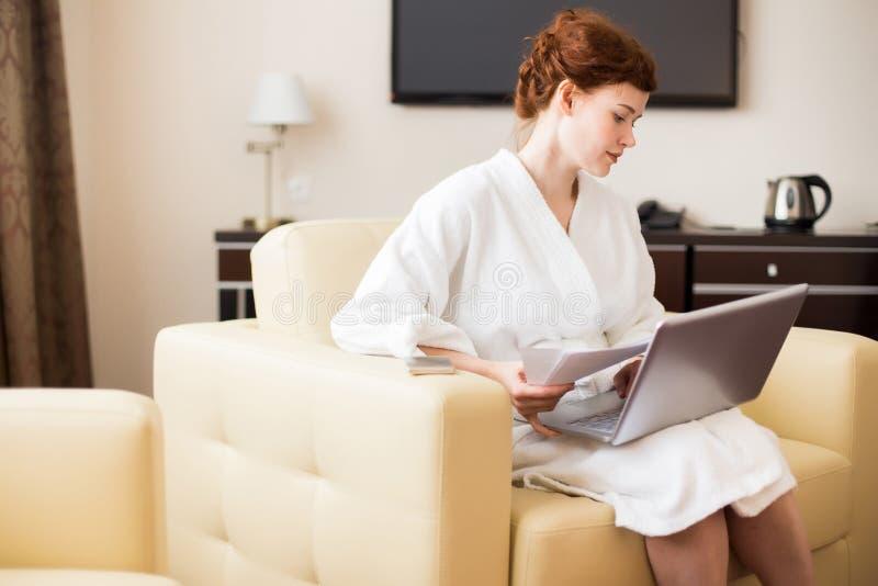 工作在旅馆客房的年轻女实业家 免版税库存图片