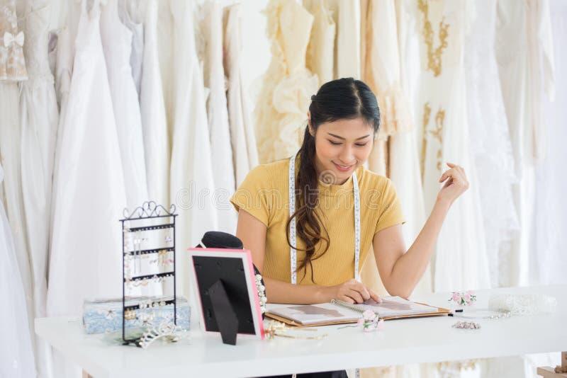 工作在时尚商店婚姻的沙龙的婚纱设计师  免版税库存图片