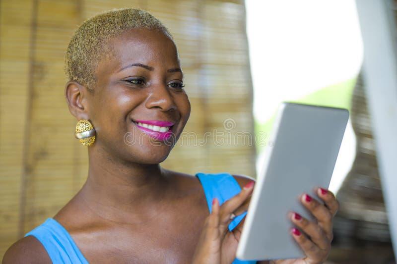工作在时髦咖啡店的年轻时髦和典雅的黑人非裔美国人的女商人使用数字式片剂垫 免版税库存照片