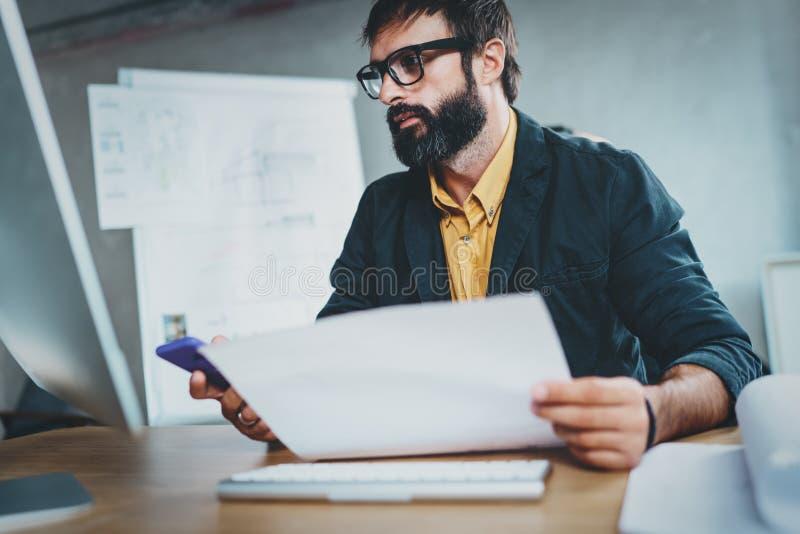 工作在晴朗的年轻有胡子的人,当坐在木桌上时 设计师分析在现代计算机上的新的想法 蠢材 库存图片