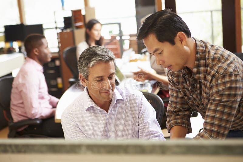 工作在有会议的书桌的两个同事在背景中 免版税库存图片