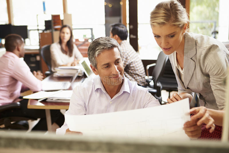 工作在有会议的书桌的两个同事在背景中 免版税库存照片