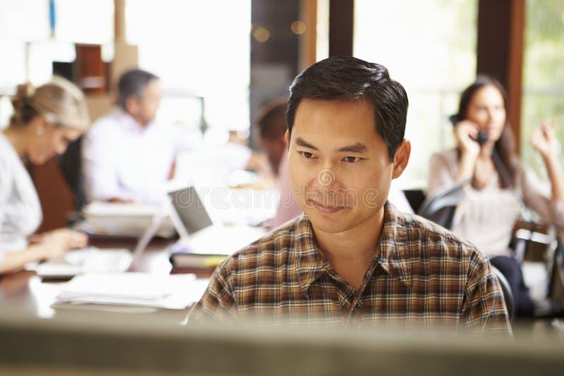 工作在有会议的书桌的商人在背景中 免版税库存照片