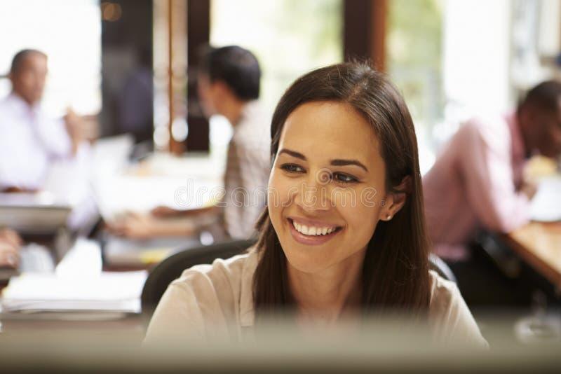 工作在有会议的书桌的女实业家在背景中 免版税库存图片