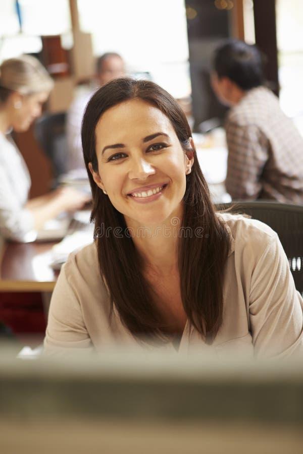 工作在有会议的书桌的女实业家在背景中 图库摄影