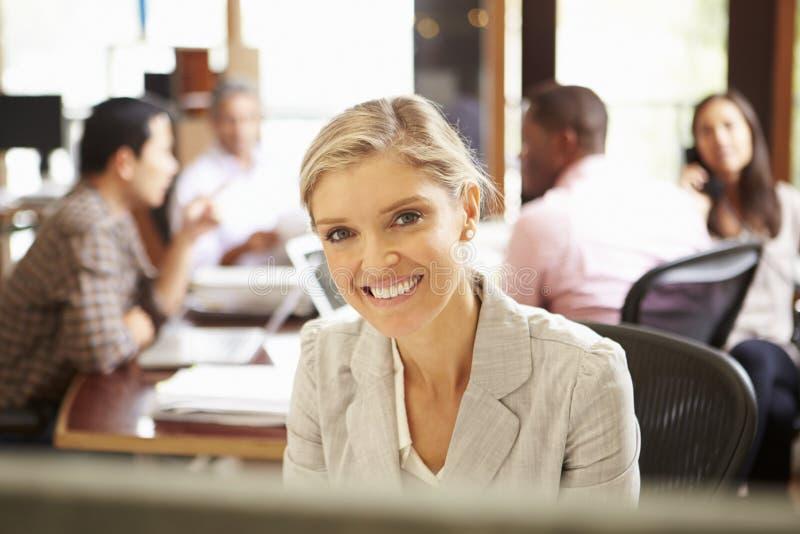 工作在有会议的书桌的女实业家在背景中 免版税图库摄影