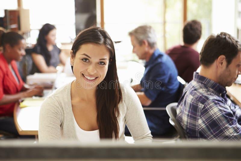 工作在有会议的书桌的女性建筑师在背景中 库存图片