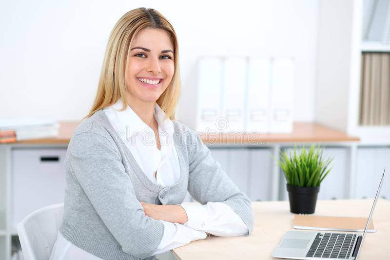 工作在有便携式计算机的办公室工作场所的年轻女商人或学生女孩 免版税库存照片