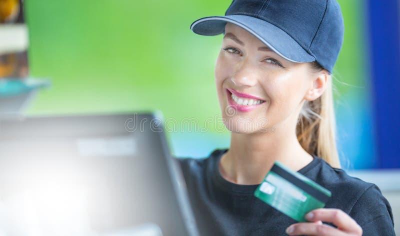 工作在有信用卡的一个收银处的可爱的少妇 免版税图库摄影