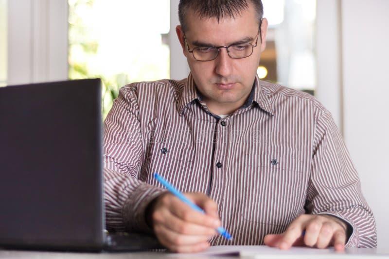 工作在有文件和膝上型计算机的现代办公室的商人 免版税图库摄影