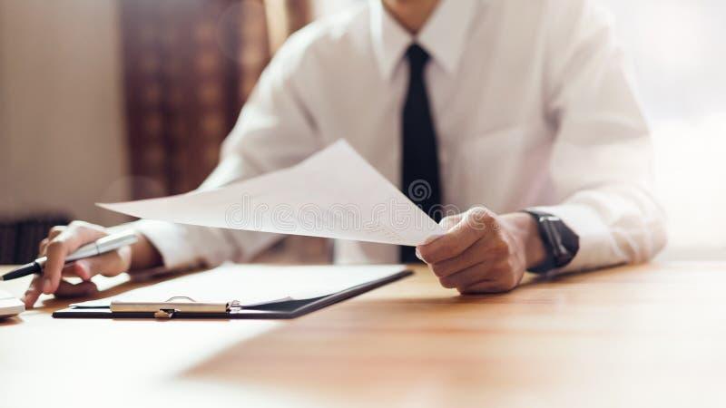 工作在有标志的办公室文件和膝上型计算机的商人 免版税库存图片