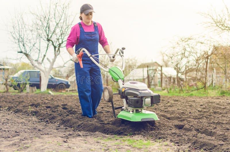 工作在有耕地机的春天庭院里的女孩 免版税图库摄影