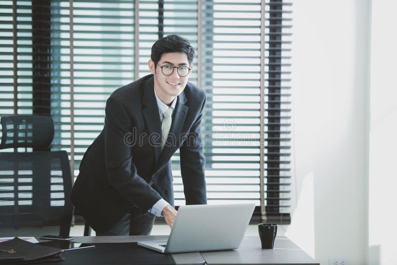 工作在有膝上型计算机的办公室的商人在他的书桌上 免版税库存照片