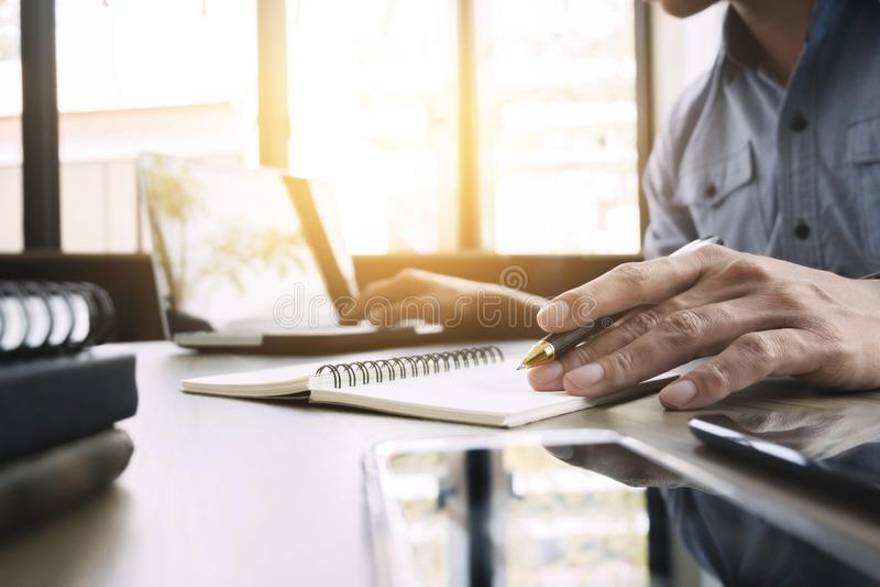 工作在有膝上型计算机的在他的书桌自由职业者概念的办公室和文件的商人 库存图片