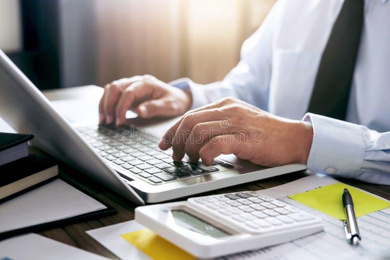 工作在有膝上型计算机的在他的办公室和文件的商人 免版税库存照片