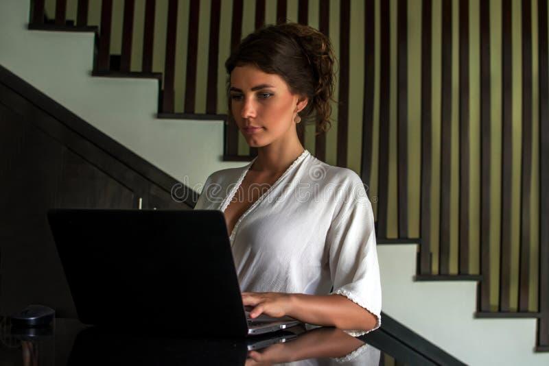 工作在有膝上型计算机的现代地方的美丽的少女 连接到互联网的女性自由职业者通过计算机 火光 免版税库存图片