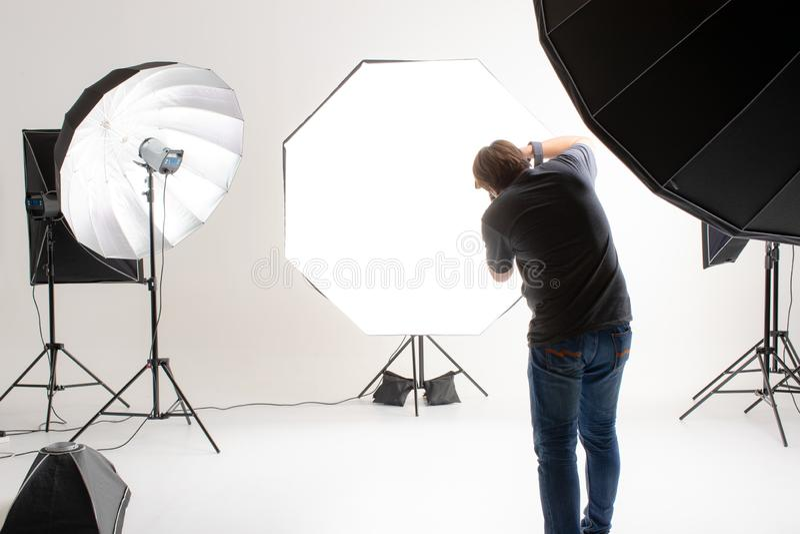 工作在有许多种类的现代照明设备演播室的摄影师 免版税库存照片