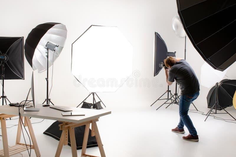 工作在有许多种类的现代照明设备演播室的摄影师 库存图片