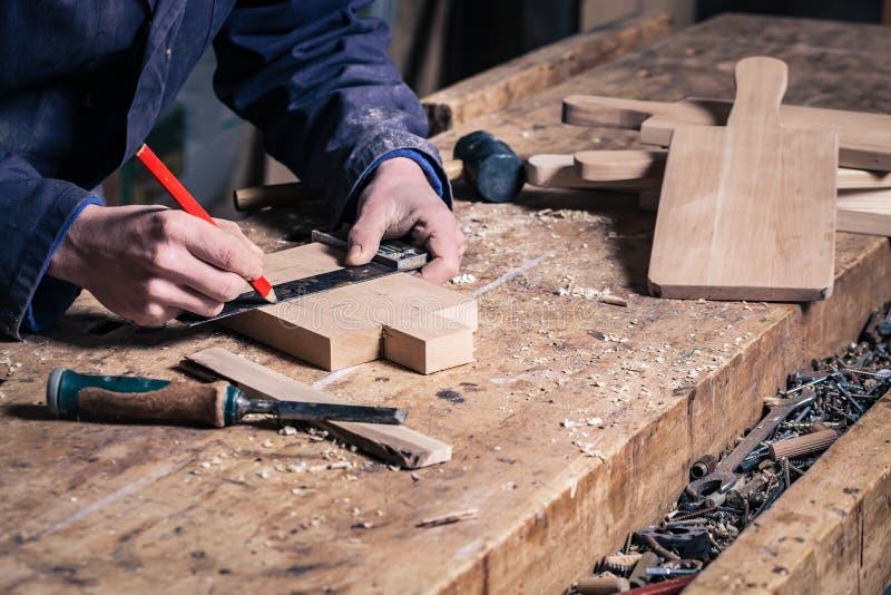 工作在有铅笔和规则的一个木切板的木匠 免版税库存照片