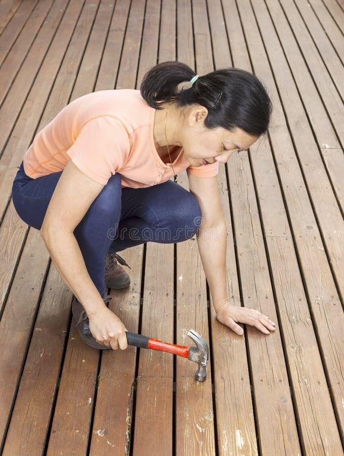 工作在有锤子的甲板的成熟妇女 图库摄影