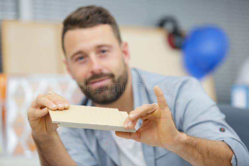 工作在有飞机的车间的木匠在木板条 免版税库存图片