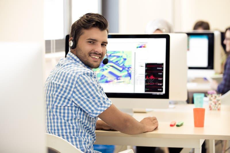 工作在服务台的人在繁忙的创造性的办公室 免版税库存图片