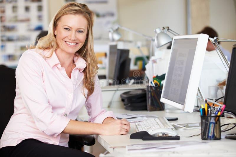工作在服务台的妇女在繁忙的创造性的办公室 免版税库存照片
