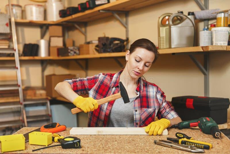 工作在木匠业车间的美丽的白种人少妇在桌地方 免版税库存图片