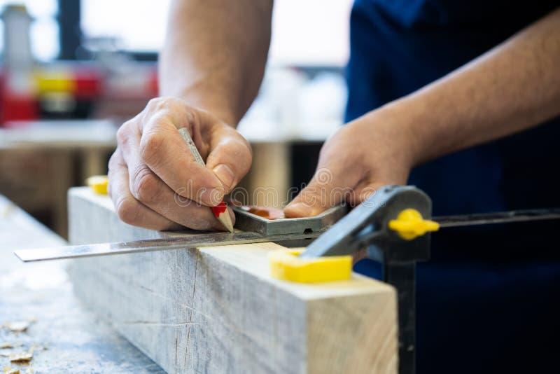 工作在木材加工机器的木匠在木匠业商店 一个人在木匠业商店工作 免版税库存图片