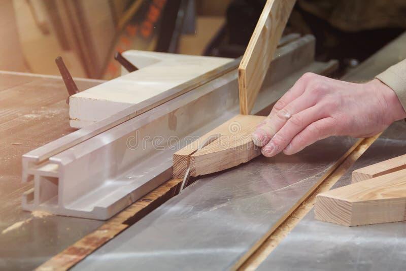 工作在木材加工机器的木匠在木匠业商店 男性手关闭 免版税库存照片