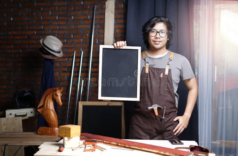 工作在木材加工车间的亚裔木匠,当举行Bl时 免版税库存图片