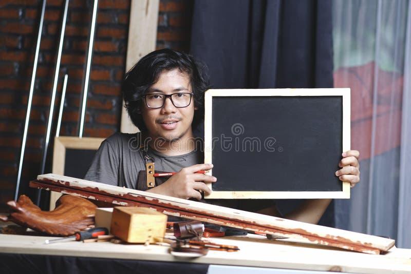 工作在木材加工车间的亚裔木匠,当举行Bl时 免版税库存照片