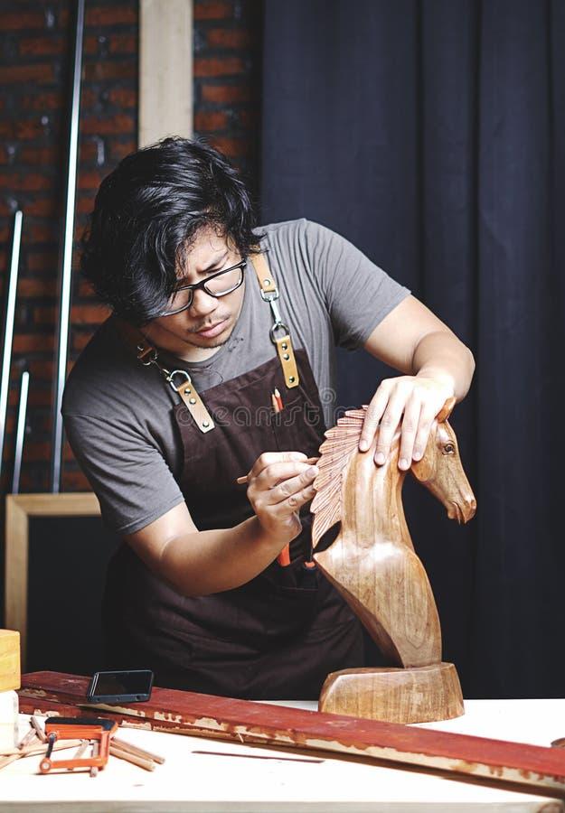 工作在木材加工车间的亚裔木匠 做木H 免版税库存图片