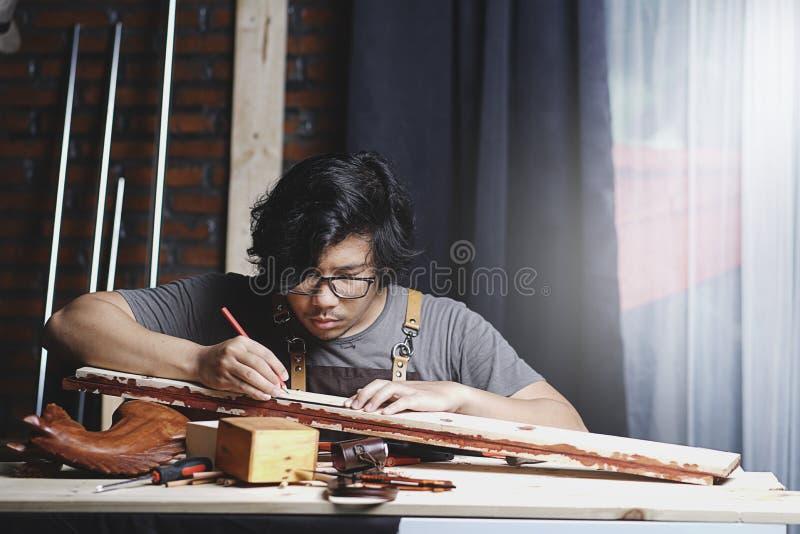 工作在木材加工车间的亚裔木匠 做线机智 免版税图库摄影