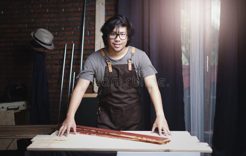 工作在木材加工车间的亚裔木匠 在照相机的微笑 库存照片
