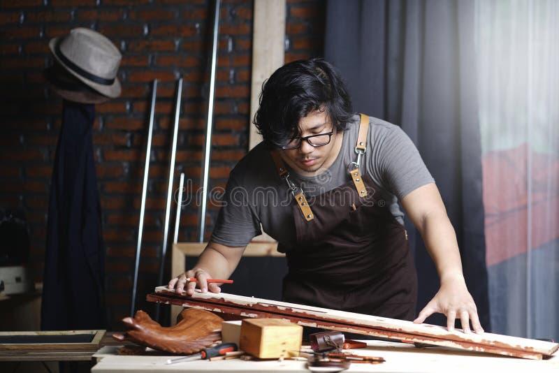 工作在木材加工车间的亚裔木匠 测量的板条 库存图片
