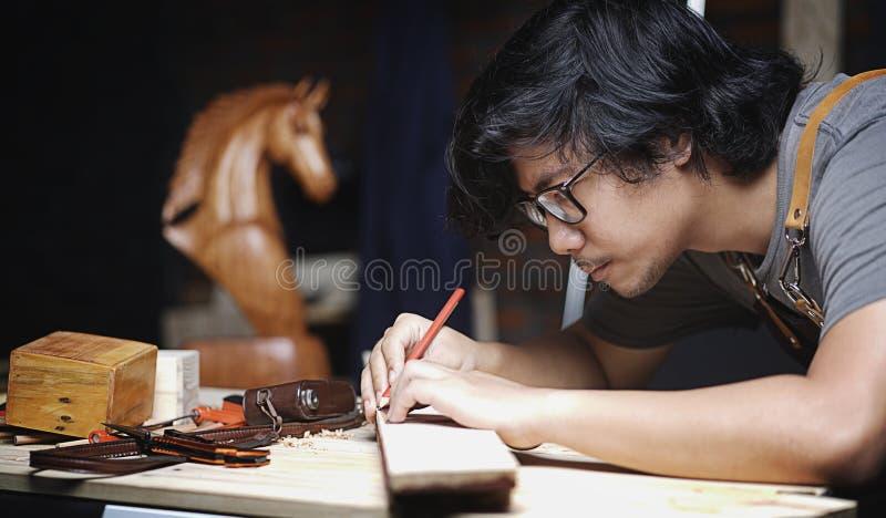 工作在木材加工车间的木匠 做与规则的线 免版税库存图片