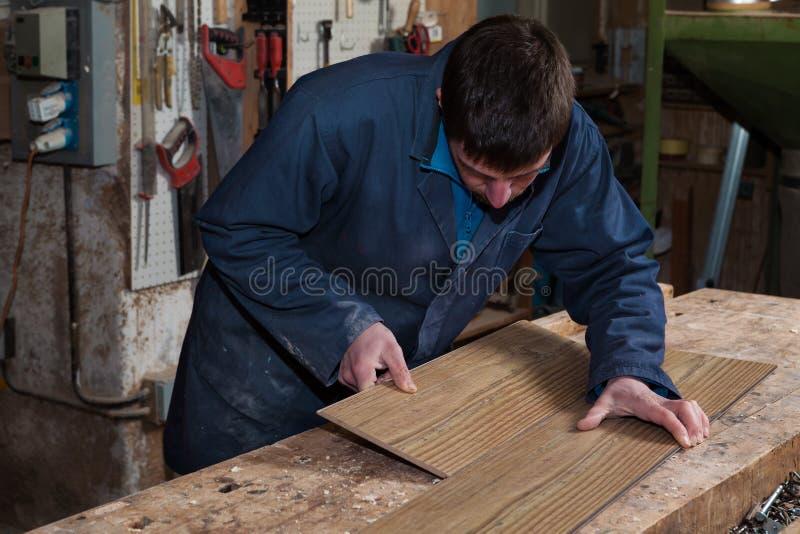工作在木板的木匠在他的车间 库存照片