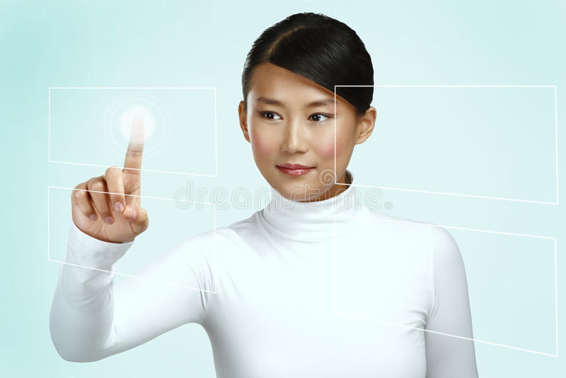 工作在未来派触摸屏幕的年轻亚裔妇女 免版税库存图片