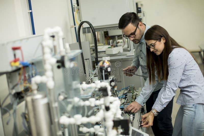 工作在机器人学实验室的学生年轻夫妇  图库摄影