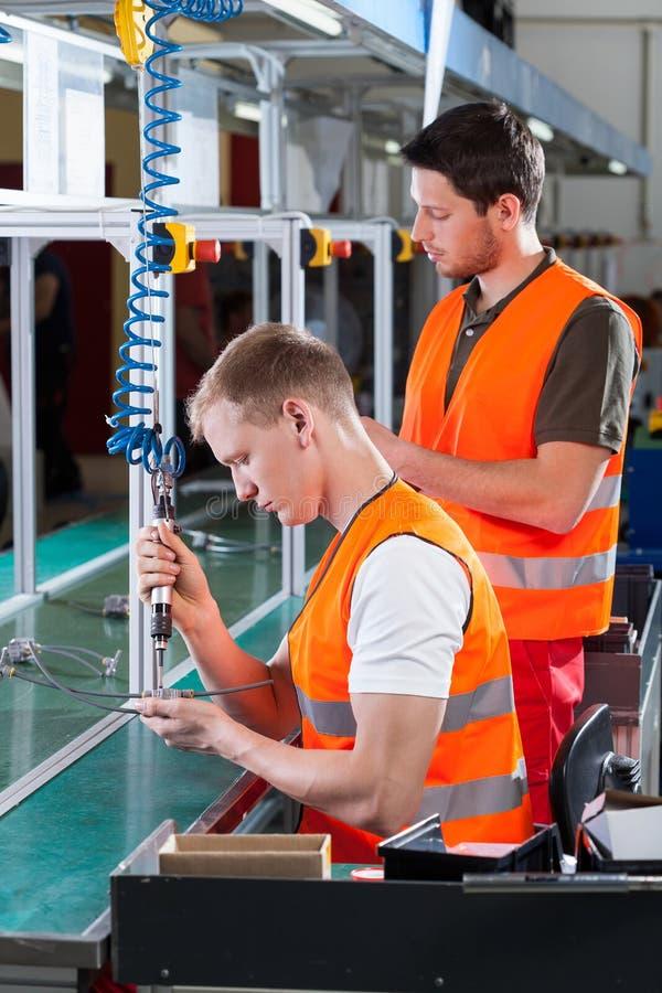 工作在机器旁边的雇员 库存图片