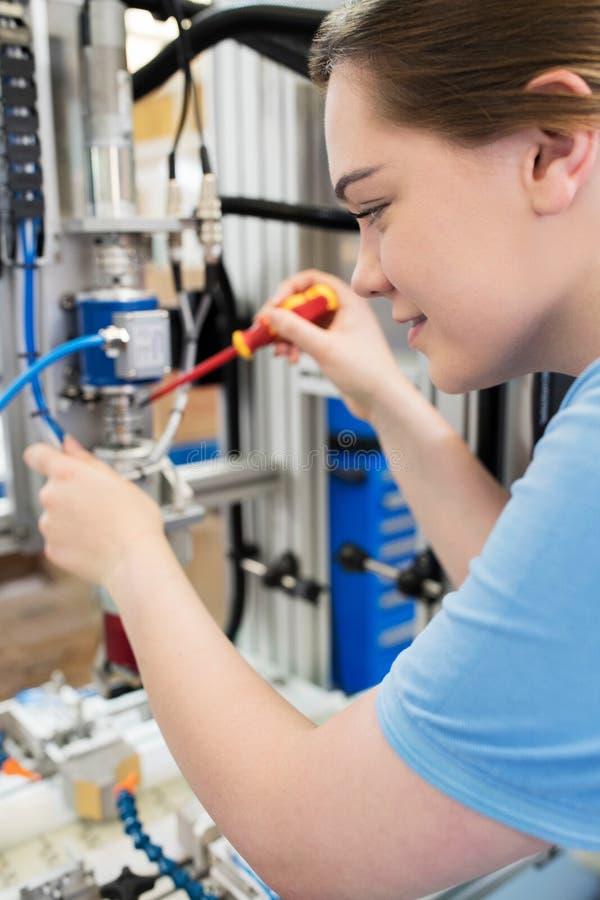 工作在机器的女性学徒工程师在工厂 库存照片
