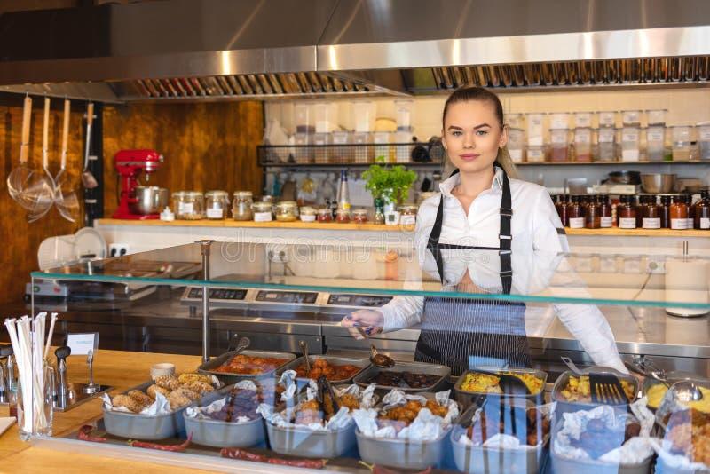 工作在柜台、年轻企业家或者女服务员服务的食物后的起始的成功的小企业主妇女, 库存图片