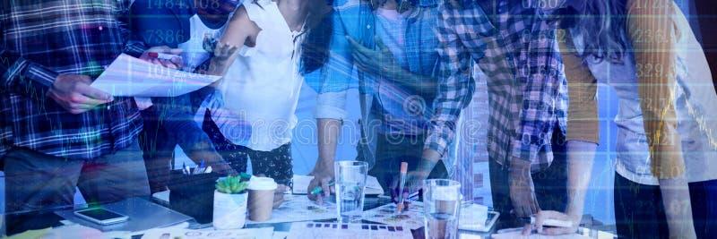 工作在桌上的微笑的商人的综合图象 库存照片